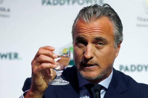 Ginola raises a glass and his profile in front of Paddy Power's backdrop