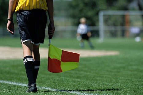 Flag at the ready. The linesman is often the least noticed participant in the football drama.