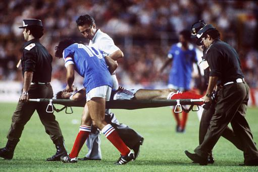 France's Patrick Battiston is carried off, escorted by captain Michel Platini.